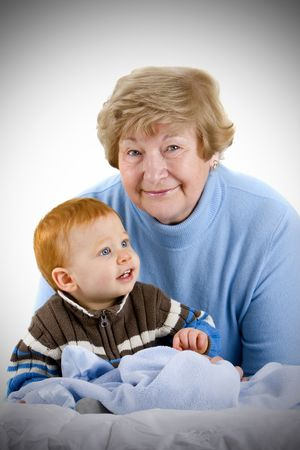 Happy grandmother with redheaded grandson sitting with blanket photo