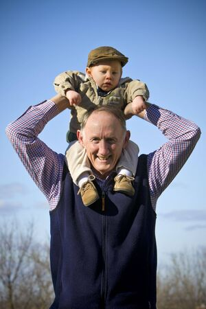 shoulder ride: Happy grandfather holding cute grandson outside