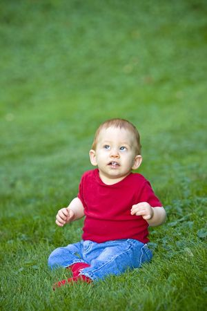 Young redheaded baby boy sitting outside on grass photo
