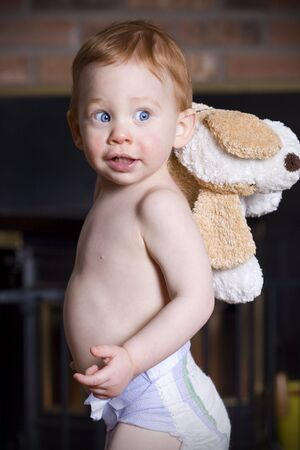 Young baby standing wearing a diaper with teddy