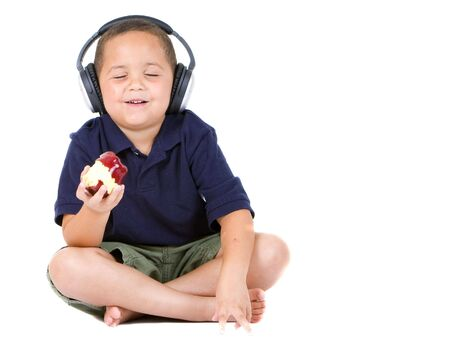 Happy boy enjoying an apple and listening to music Stock Photo - 4169162