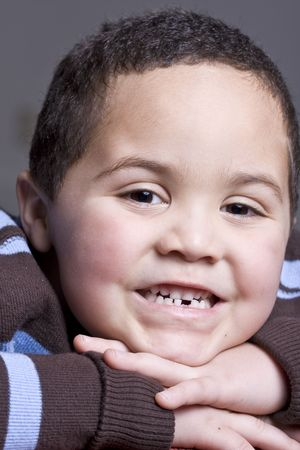 Young boy with missing baby tooth smiling photo