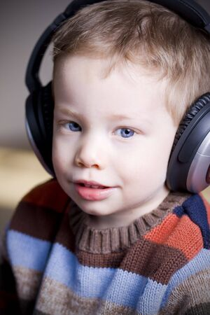 Cute young boy listening to music on headphones photo