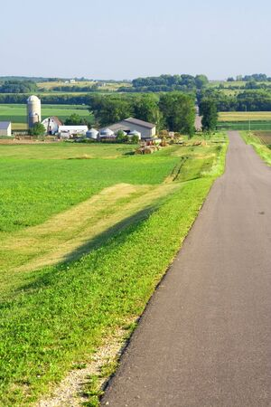 Summer field and road with farm in background Stock Photo - 4252619