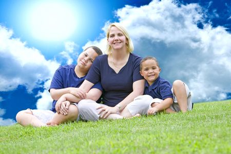 Pretty mom with her two sons outside on grass photo