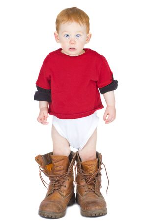 muddy clothes: Baby boy standing in an adult pair of work boots Stock Photo