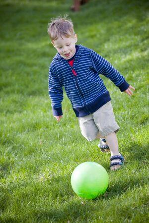 Cute boy having fun kicking toy ball Reklamní fotografie