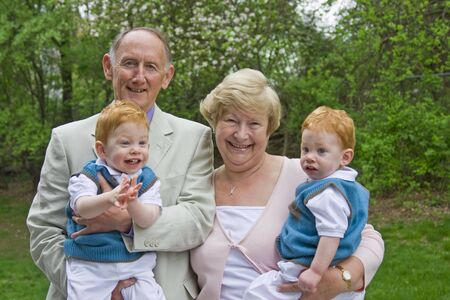 grand sons: Grandparents holding twin grandsons in garden