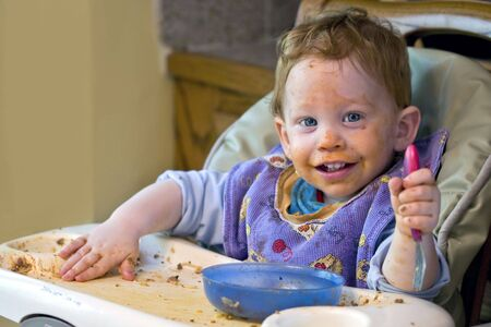dinnertime: Messy baby covered in food during mealtime Stock Photo
