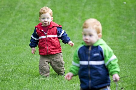 Twin boys playing outside on grass photo