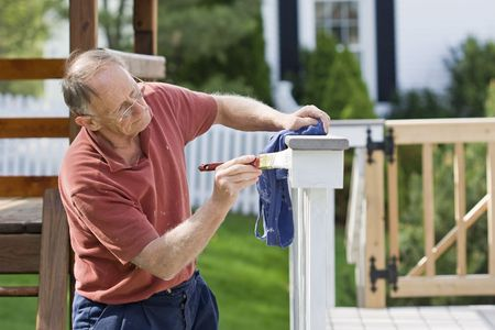 Mature man painting fence outdoors photo