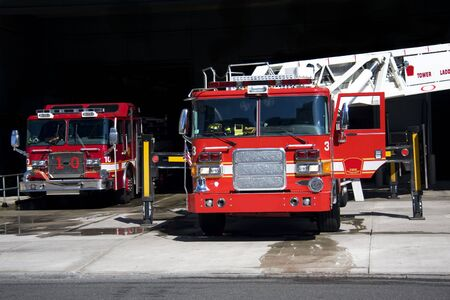Two fire trucks parked in the bay with all of the fire fighting equipment and gear ready to go Stock Photo