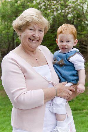 Grandmother holding grandson in garden