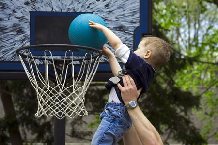 Adult helping boy score a basketball shot