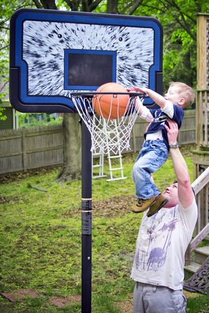 Adult helping boy score a basketball shot