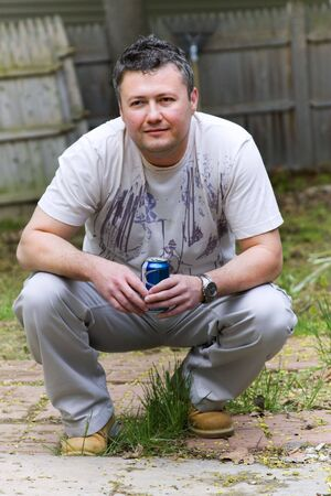 Man crouching and smiling with a can of beer