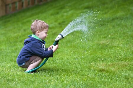 hosepipe: Handsome young boy watering garden with rubber hosepipe Stock Photo