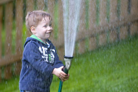 Handsome young boy watering garden with rubber hosepipe 스톡 콘텐츠