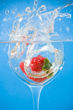 Strawberry splashing into wine glass underwater photo