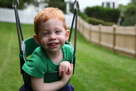 Happy boy sitting in swing outside Stock Photo