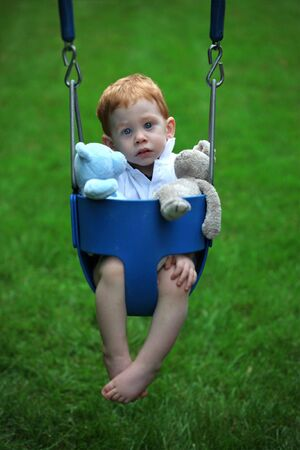 Cute boy sitting on swing with soft toys photo