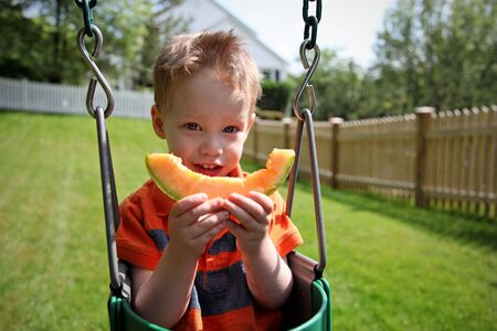 Young boy sitting outside eating melon photo