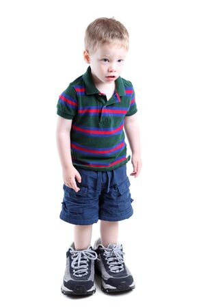 Boy wearing big sneakers isolated on white Stock Photo