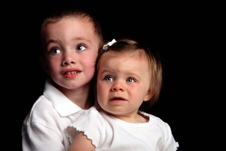 Brother and sister sitting in studio with focus on baby girl Stock Photo - 5215913