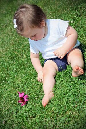 9 months: Beautiful baby girl looking at flower