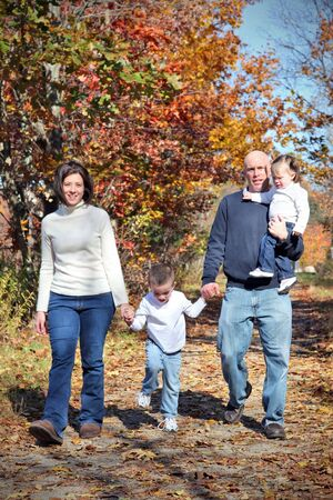 Happy family walking on path during autumn photo