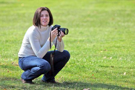 Pretty woman crouching with camera photo