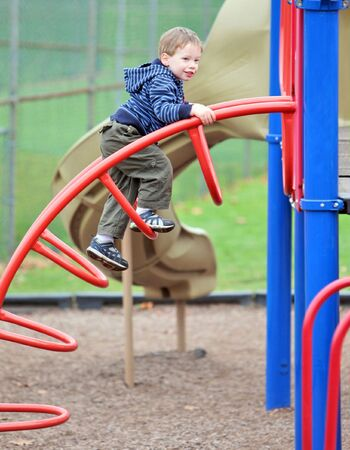 Cute boy climbing on park climbing frame