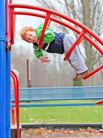 climbing frame: Ragazzo carino arrampicata sulla scalata cornice del parco