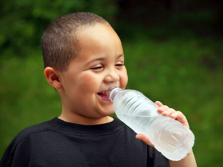 Smiling latino boy portrait outdoors drinking water