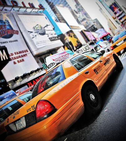 Yellow Cab in high contrast color and vignette speeding through Times Square New York