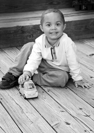 Young toddler boy playing with car photo