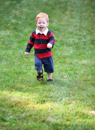 Happy boy running down hill photo