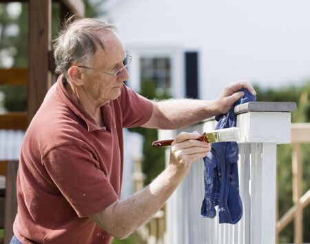 man painting: Senior man painting a wooden decking fence Stock Photo