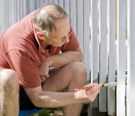 decking: Senior man painting a wooden decking fence Stock Photo