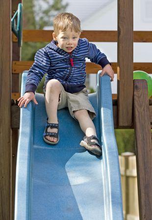 Nervous boy at the top of a slide