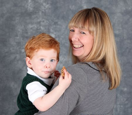 Pretty woman holding a cute red haired boy eating a cookie Stock Photo - 6927003