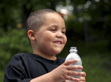 Happy Latino boy holding a plastic water bottle photo