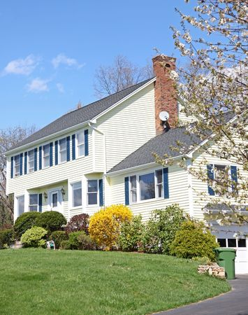 Yellow New England Style colonial house on a spring day