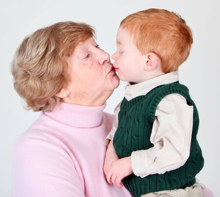 Grandmother giving a kiss to her grandson photo