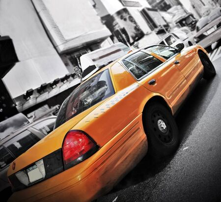 Yellow Cab in high contrast color and vignette speeding through Times Square New York photo