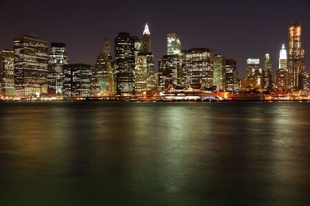 Lower Manhattan in New York City at night with reflection in water