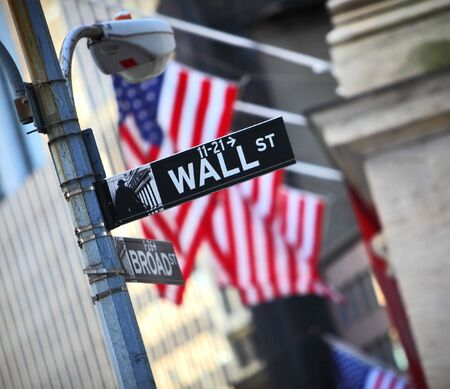 main market: Wall Street sign and flag background in New York City