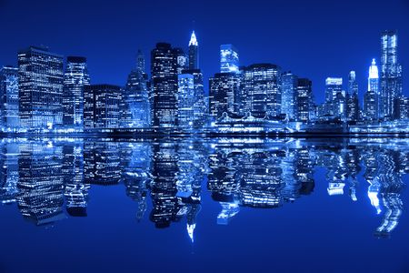 Lower Manhattan in New York City at night with reflection in water with blue hue photo