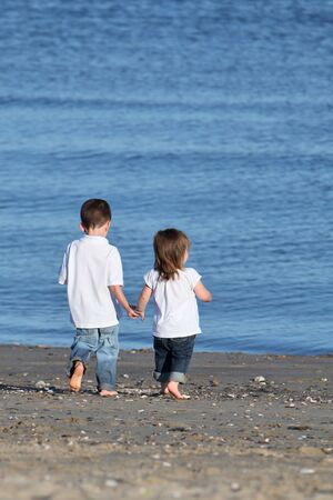 Brother and sister walking hand in hand at the beach photo