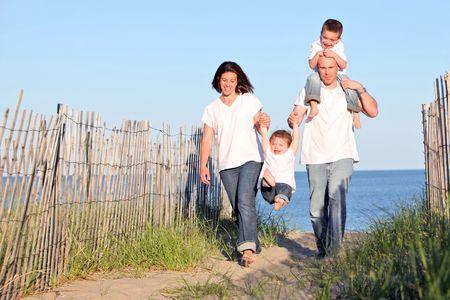 sandy: Buen aspecto ir familiar a dar un paseo en la playa al atardecer  Foto de archivo